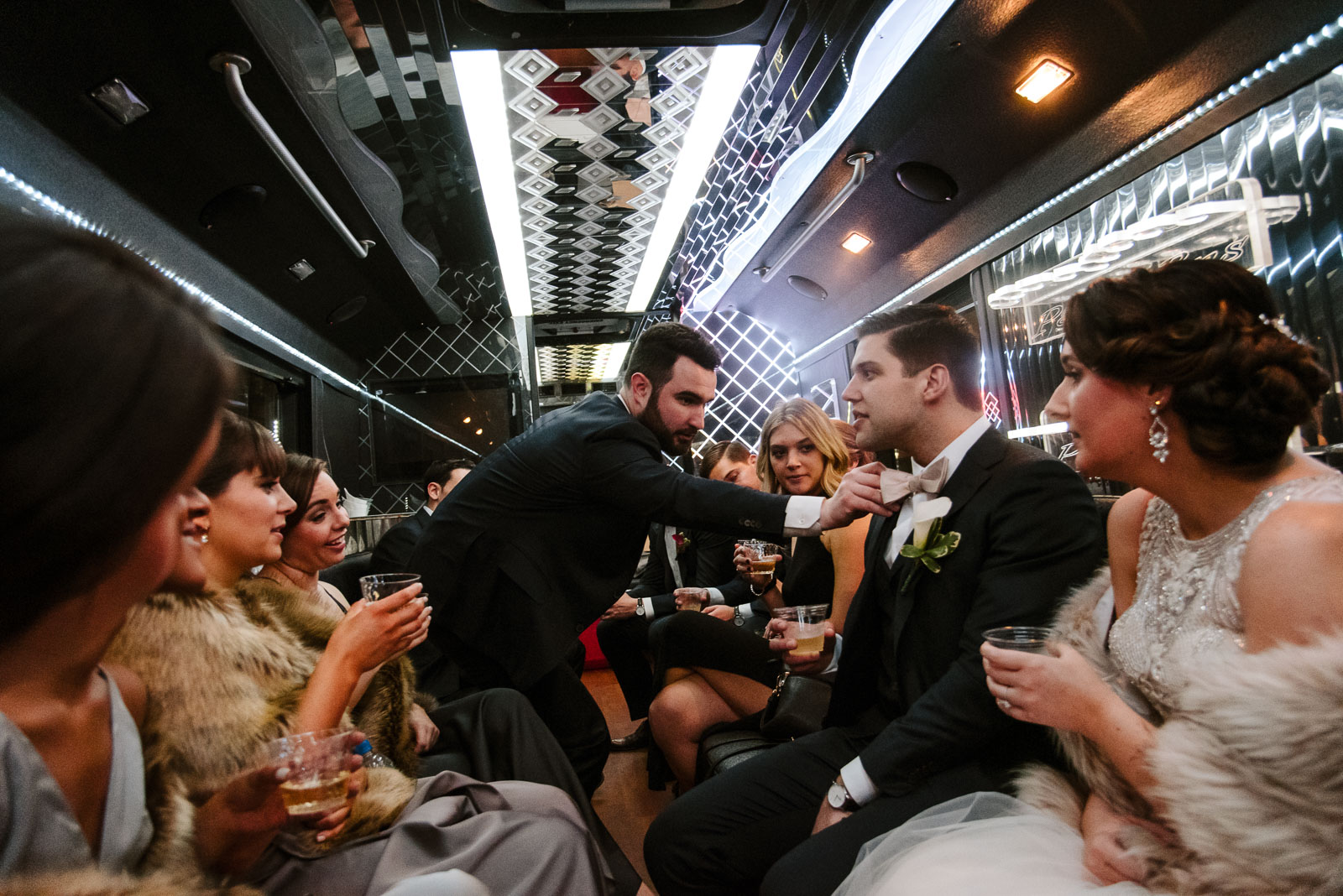 Groomsman helps groom with his tie in a limo