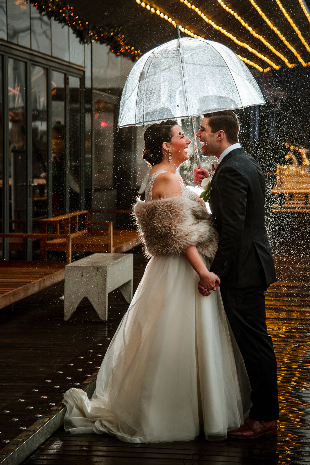 Bride and groom portrait in the rain with umbrella