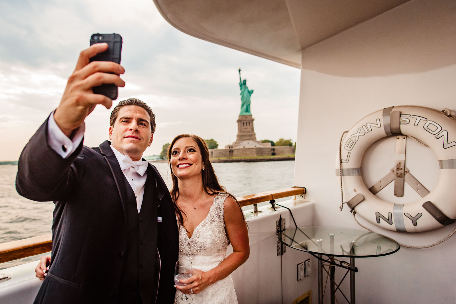 bride and groom take selfie with statue of liberty