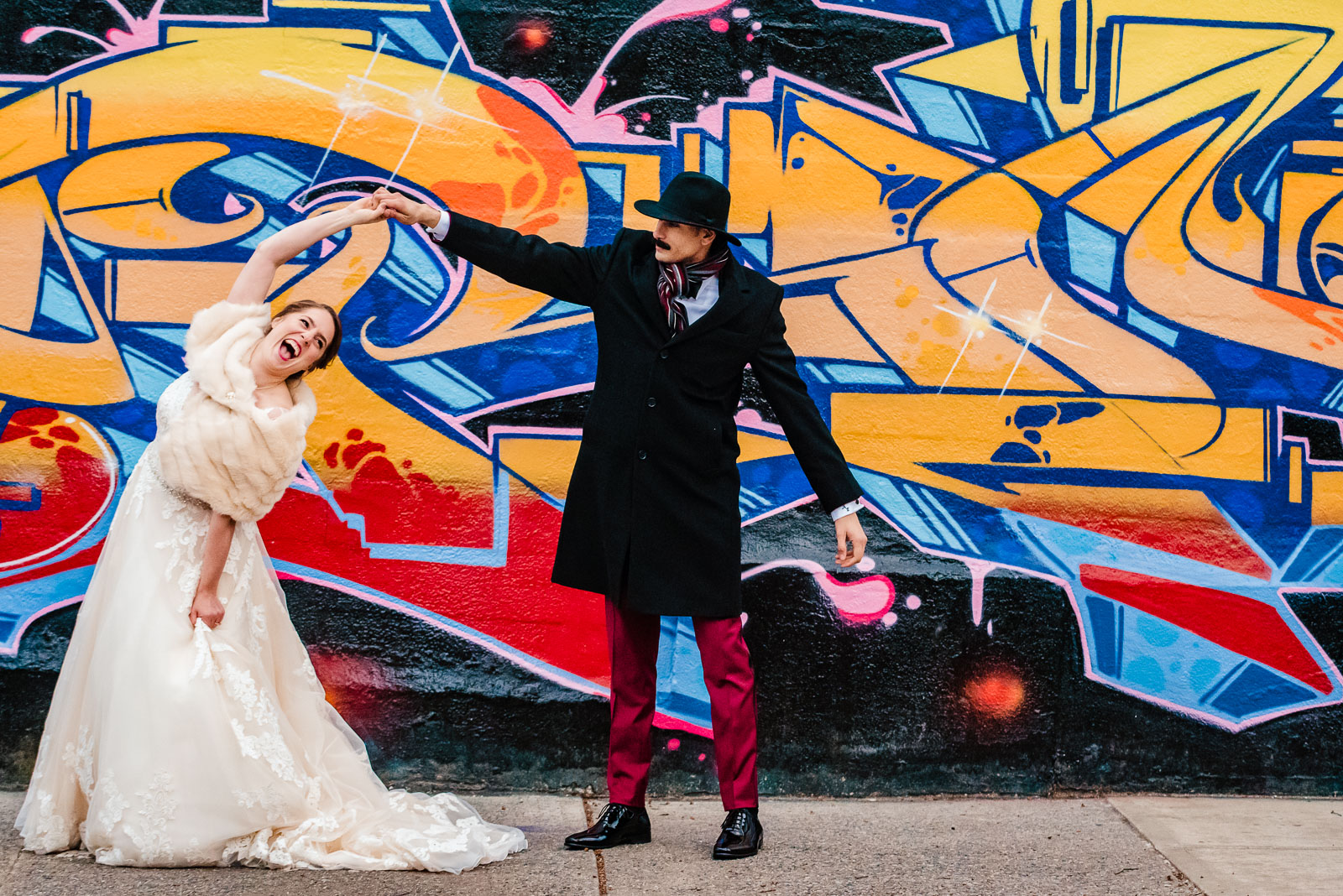 Bride and groom dance on a street