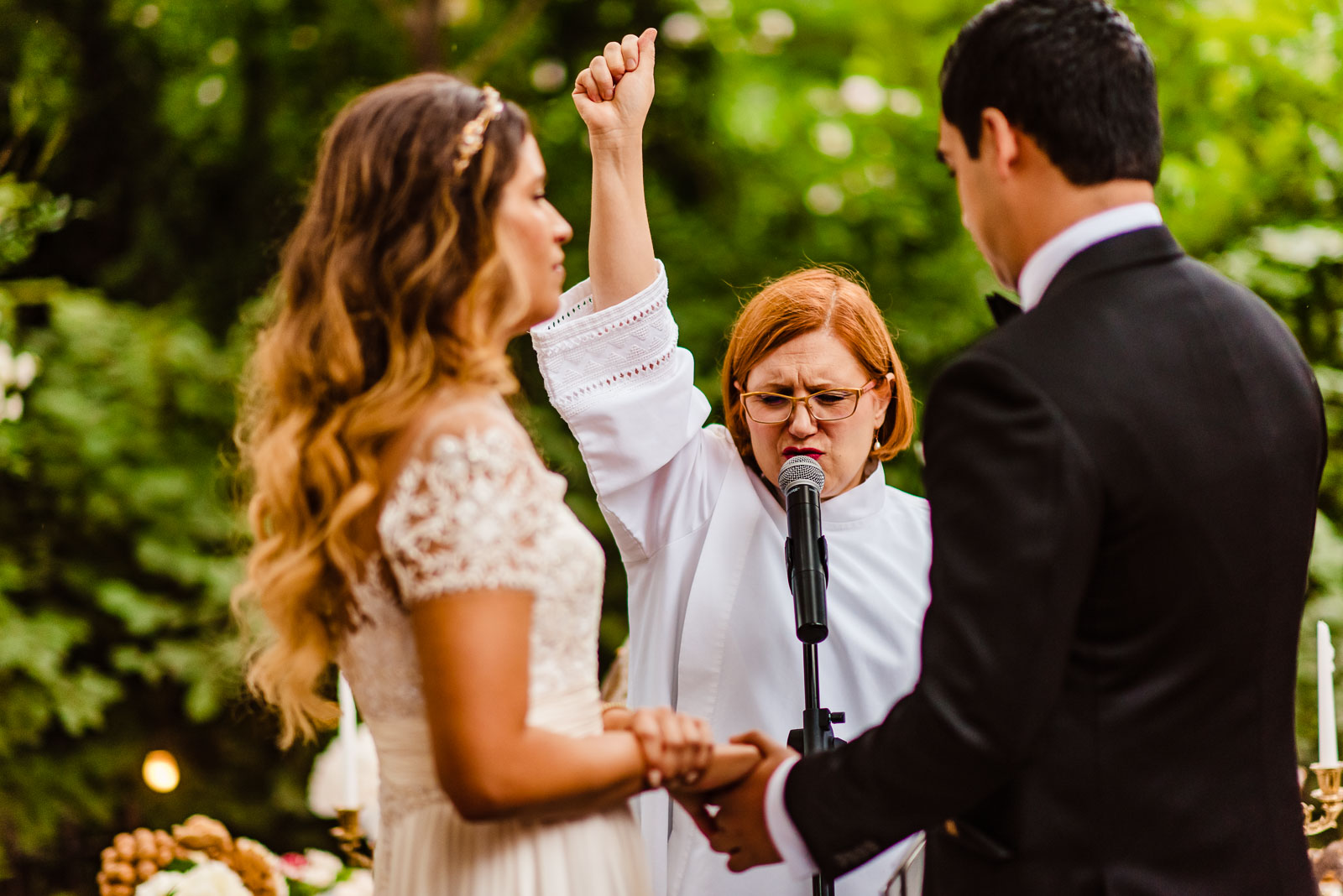 Officiant raises ring above bride and groom