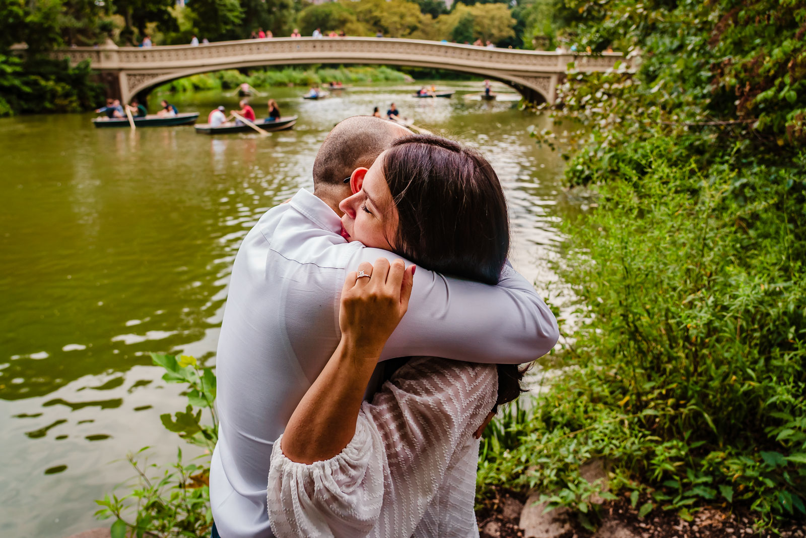 Couple hugs after proposal near Bow Bridge in Central Park