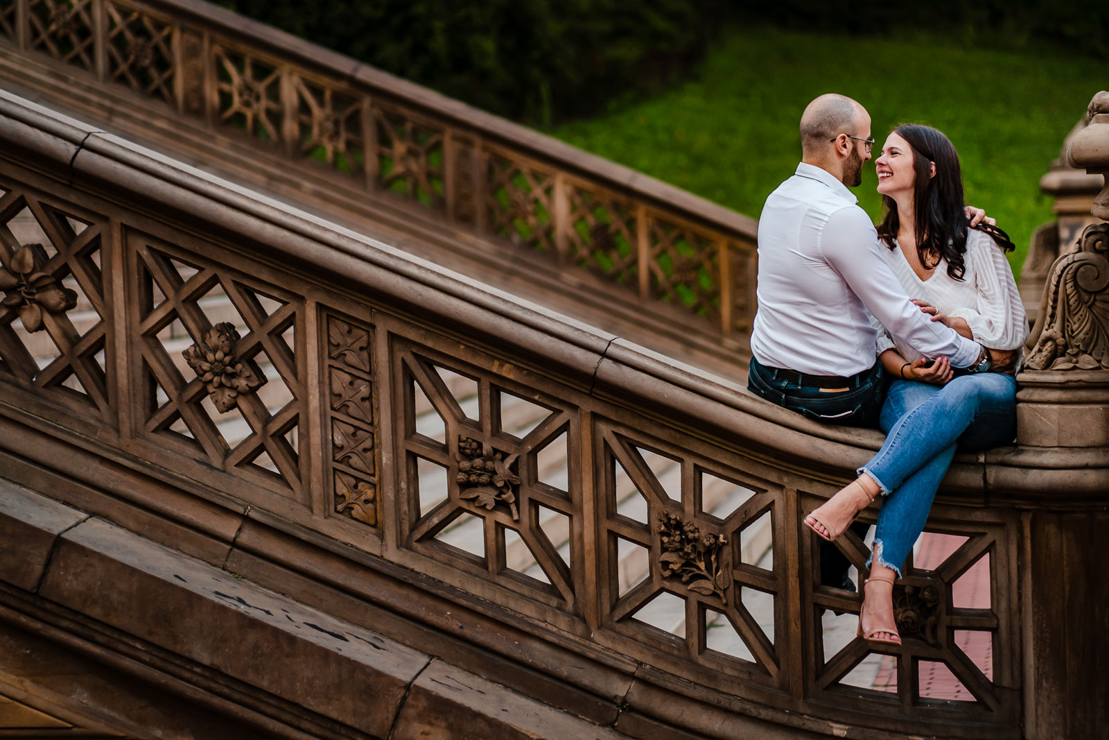 Newly engaged couple having laughs on steps of bethesda terrace