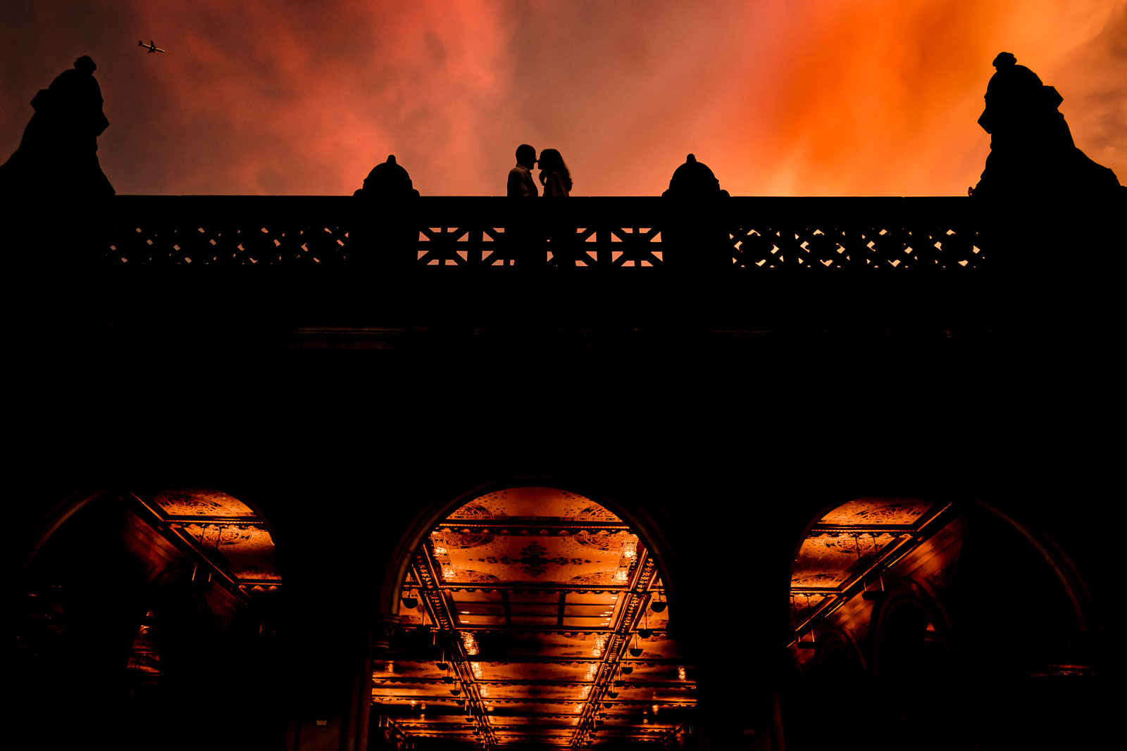 Couple silhouette with orange-red sunset at bethesda terrace in Central Park