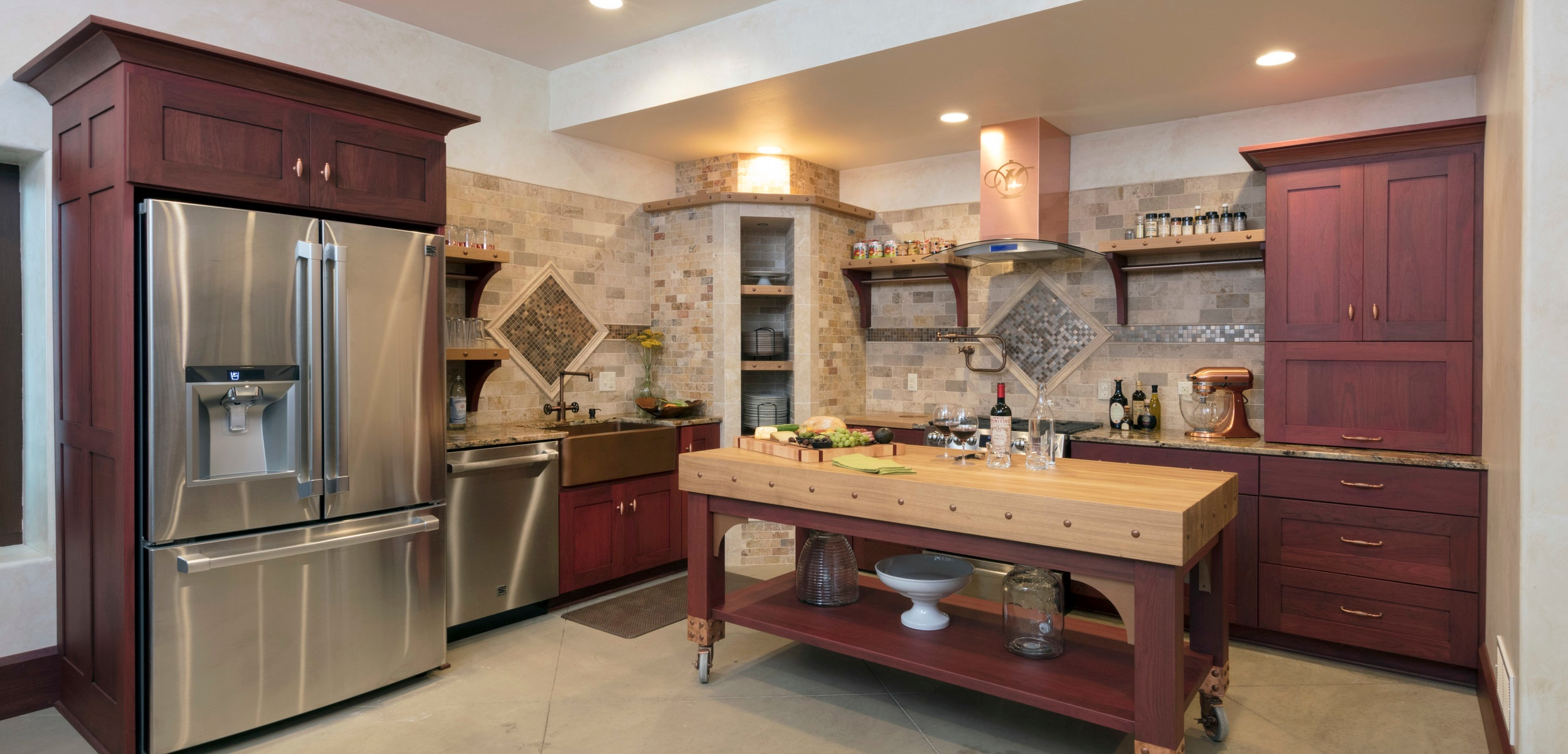 rustic, organic textures and materials meet to give this kitchen an inviting, romantic feel that welcomes everyone into the kitchen. THE RICH COLORS OF THE HARDWOOD OFFSET THE DELICATE SHADES IN THE TILE, CREATing A WARMING FEEL FOR THE SOFTER WOOD SURFACES, CLEAN REFLECTIVE METALS, AND COZY LIGHTING.