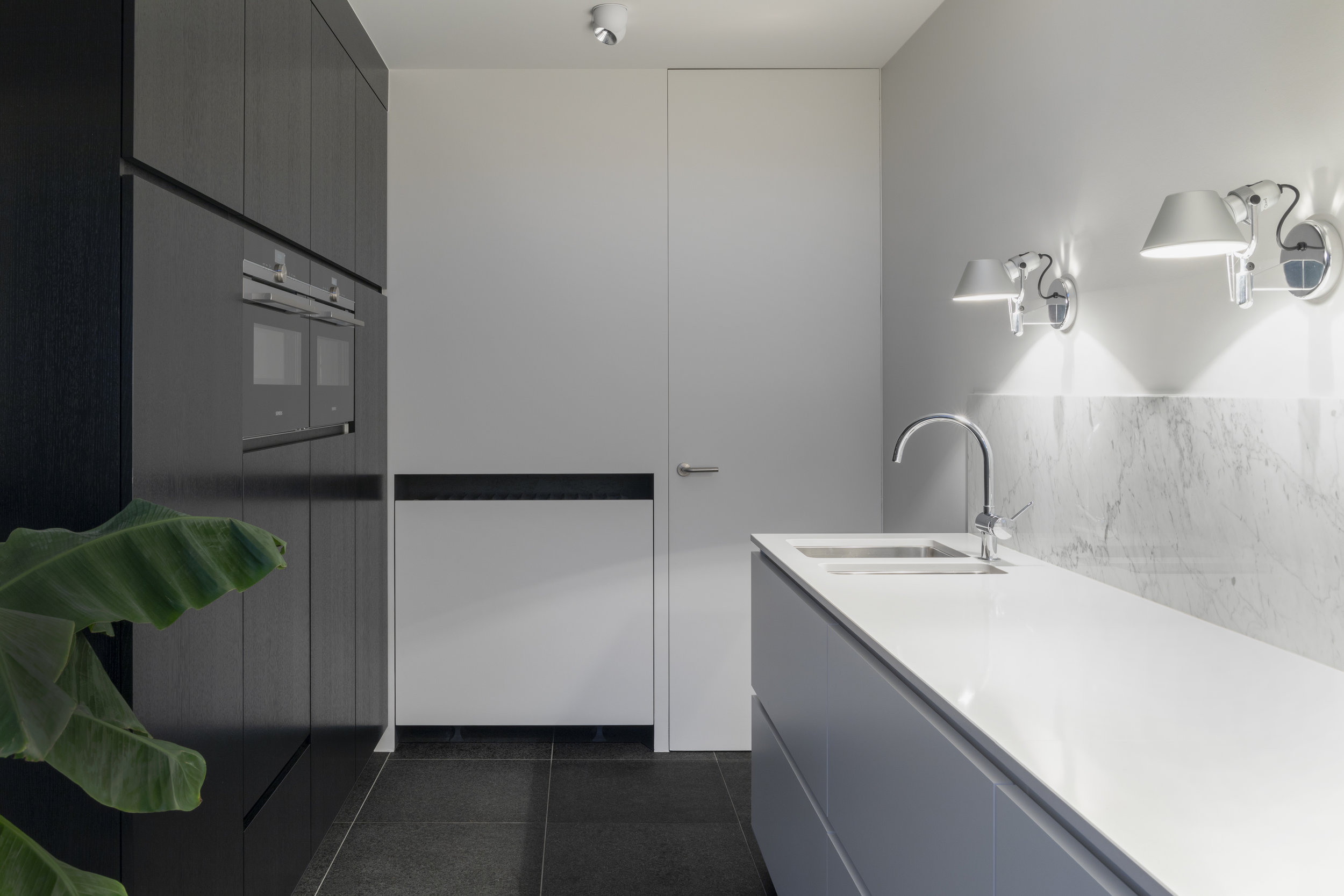 A simple WHITE KITCHEN DESIGN IS ELEVATED THROUGH CONTRAST WITH BLACK APPLiaNCES AND DARK CABINETS.