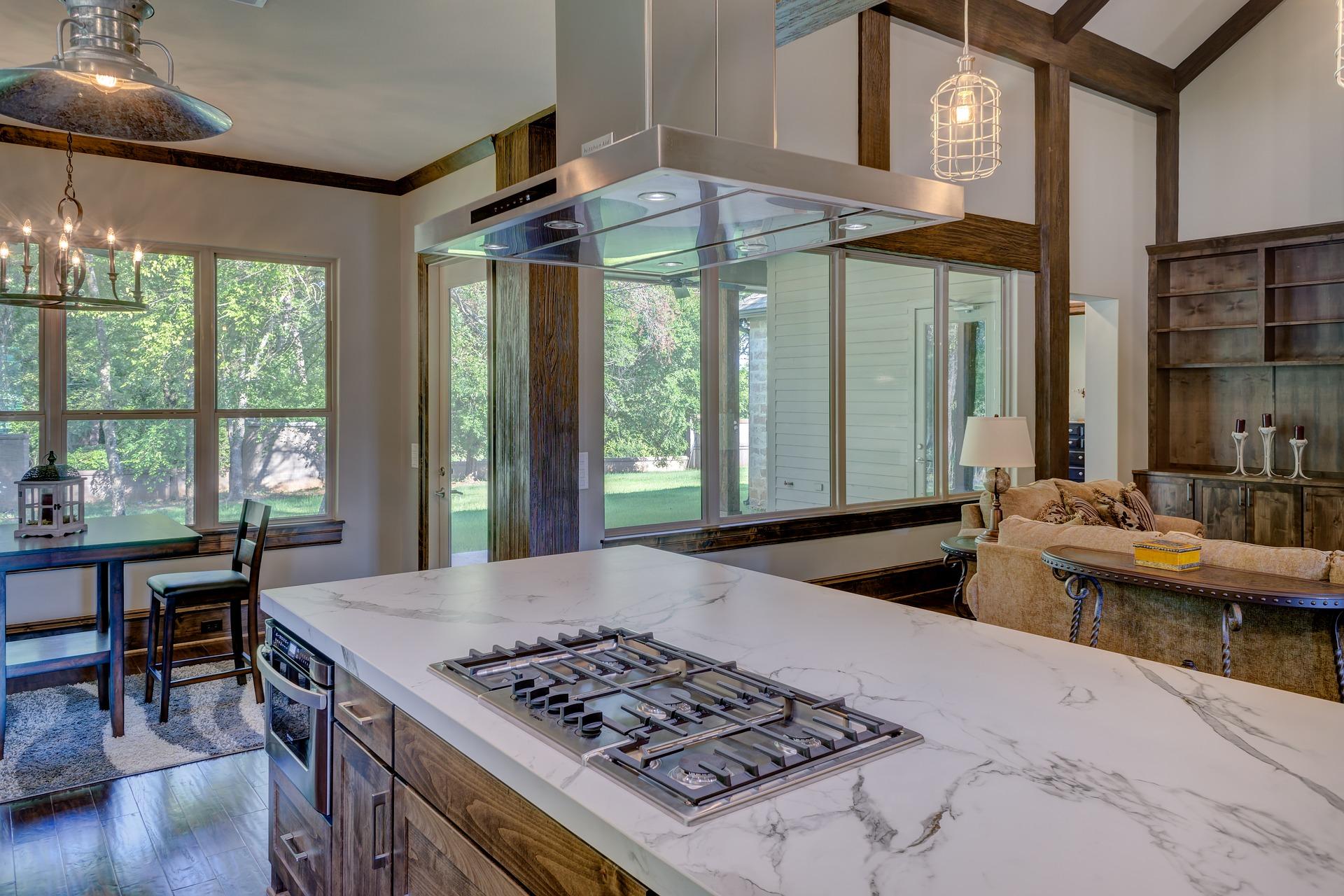 stainless steel island range hood installed over an island drop-in cooktop.