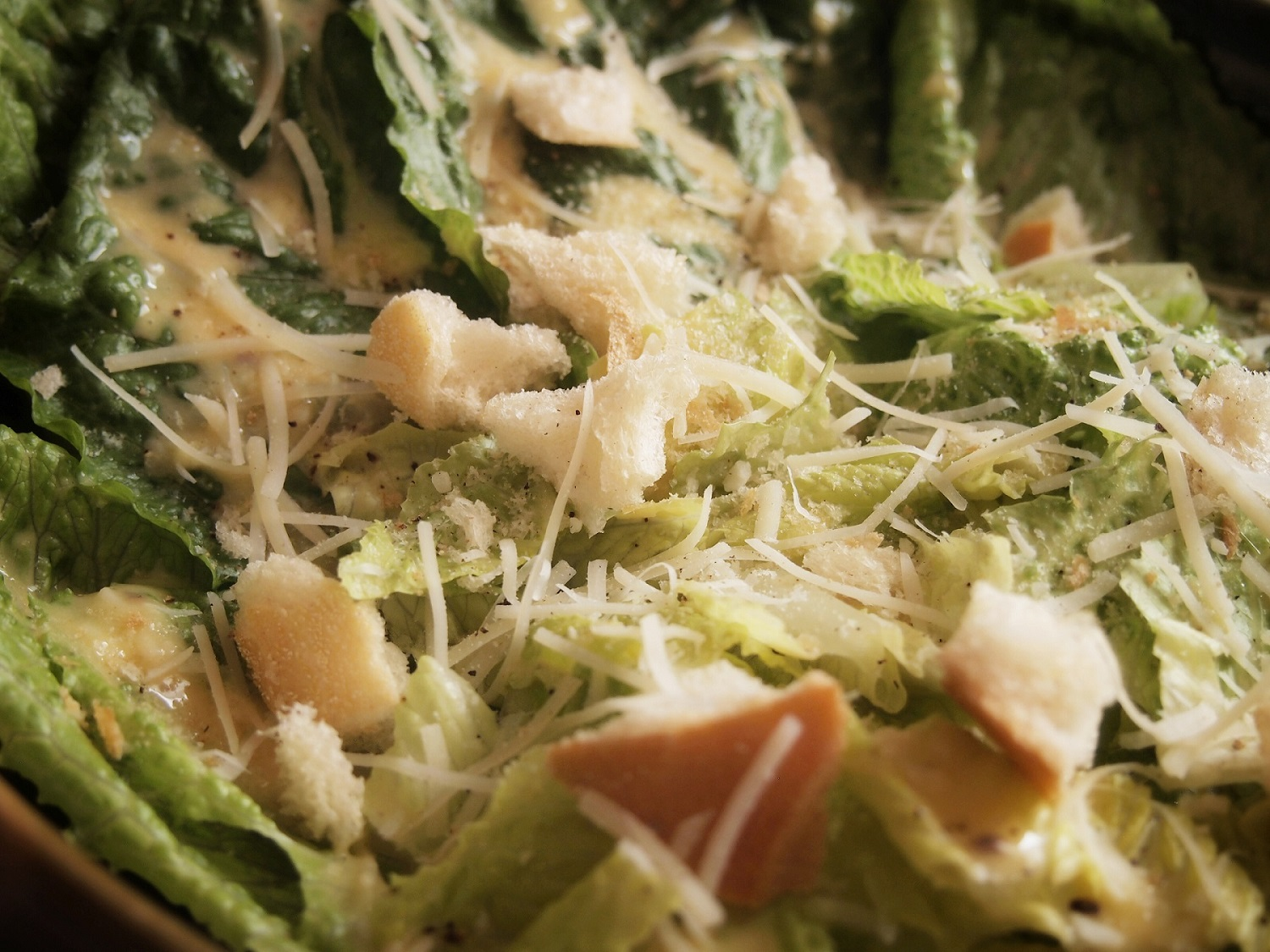 Close up of the Caesar salad recipe with croutons, Parmesan cheese, and romaine.