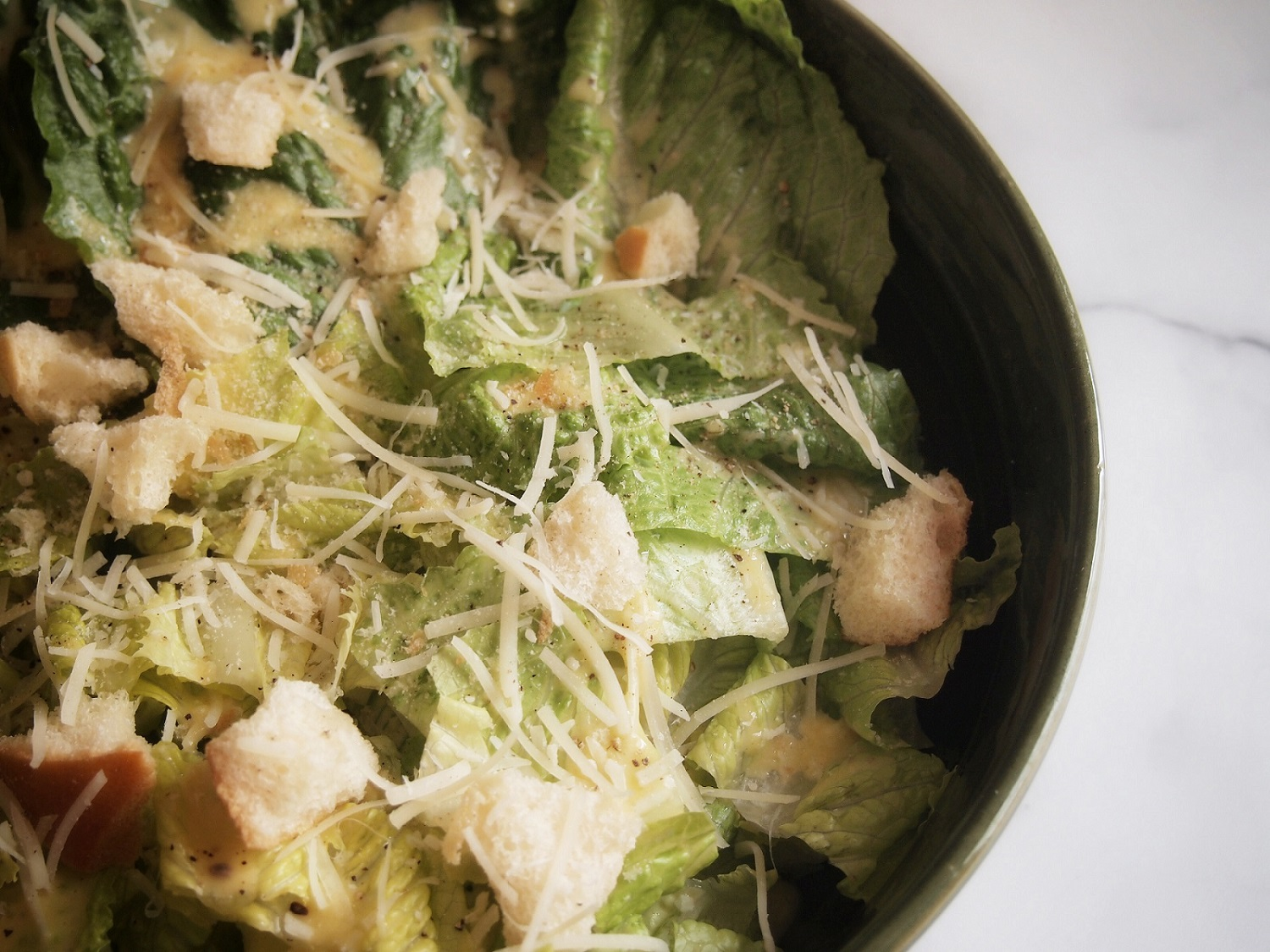Close up of the Caesar salad recipe with crouton, cheese, and romaine on a marble panel.