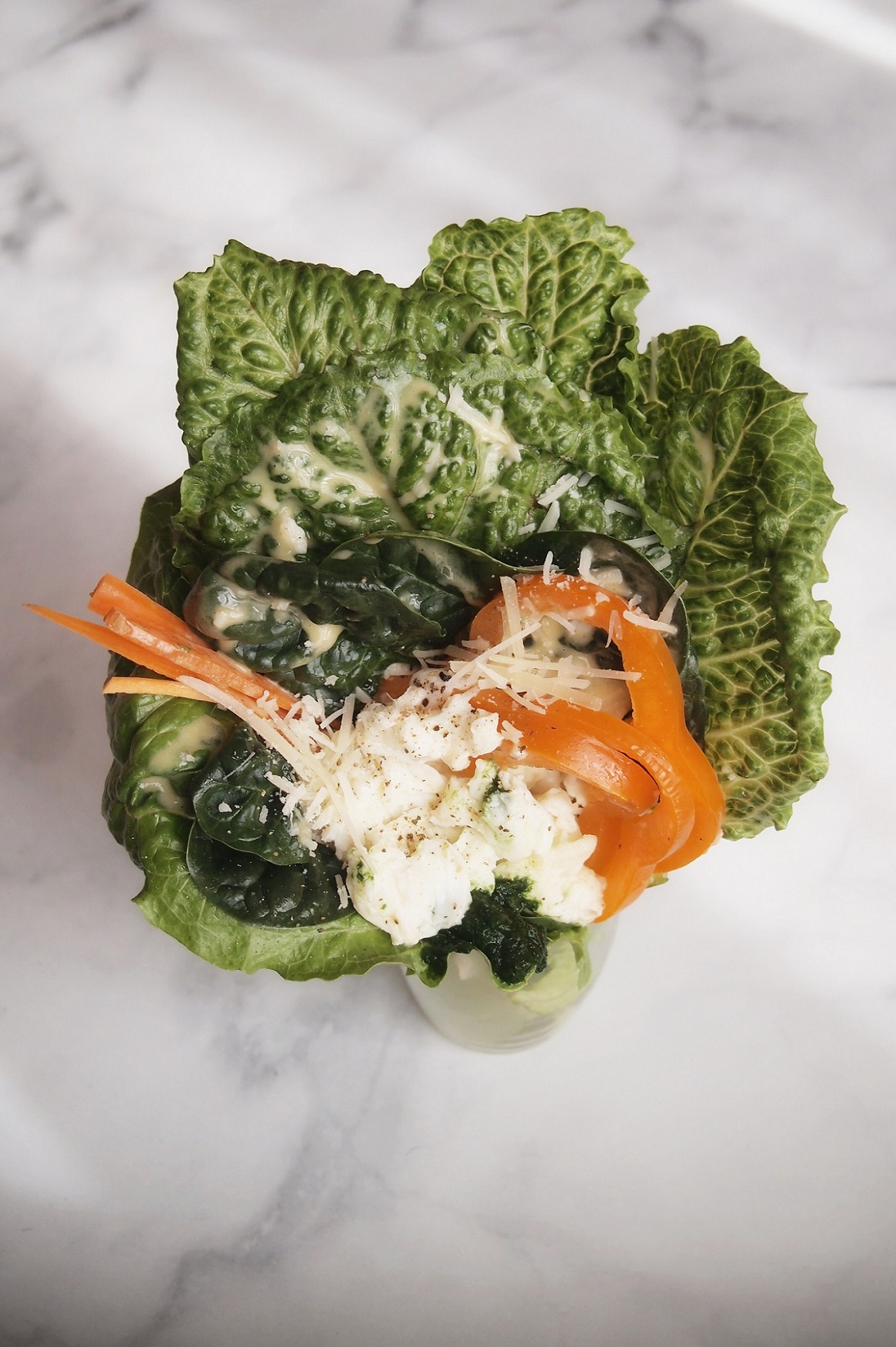 Caesar salad bouquet in a glass vase on top of marble setting.