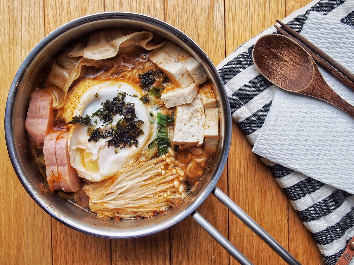 The Lazy Sunday Ramen Broth in a pan on a wooden board.