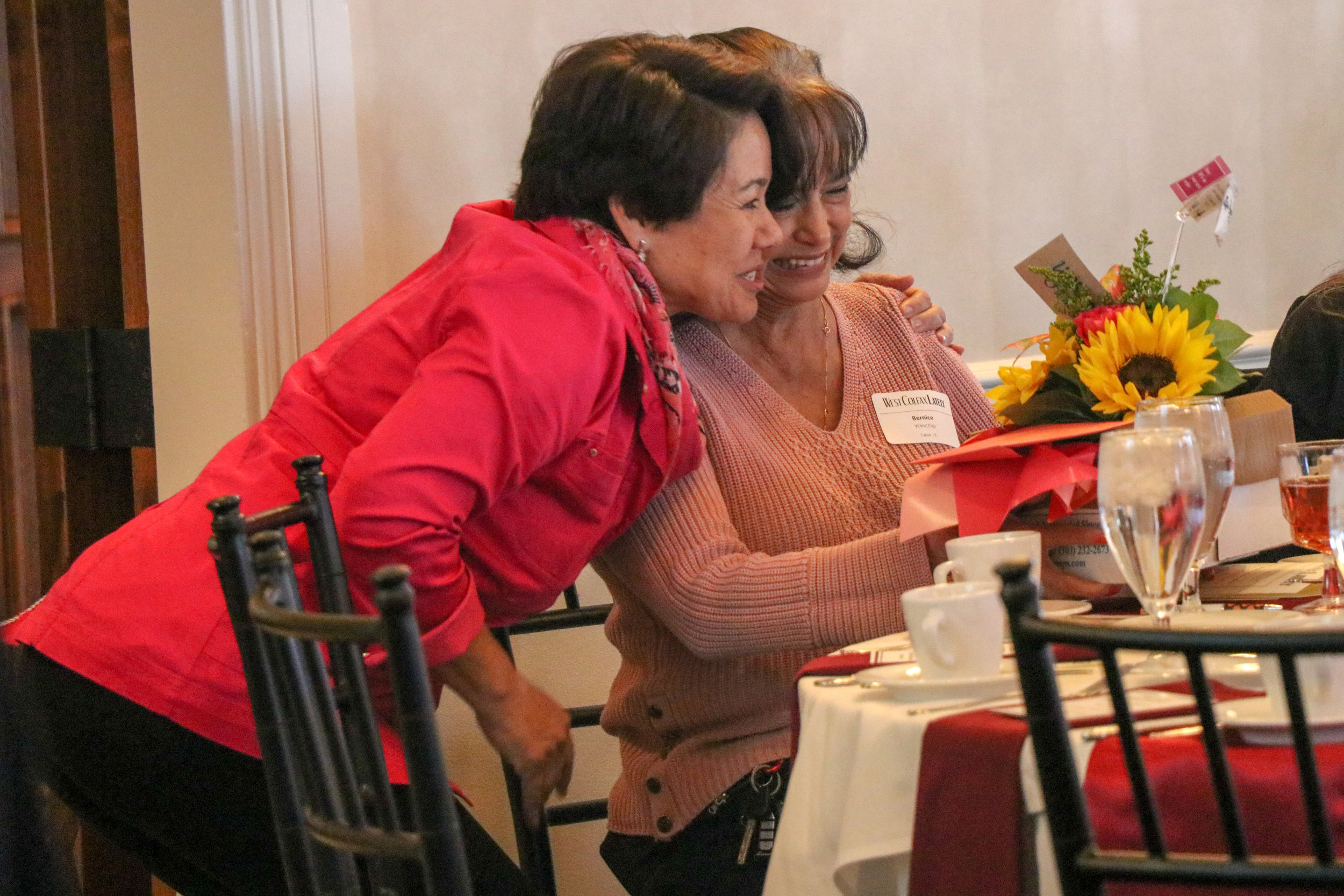 Cindy Baroway hugs Bernice Winchip of Guidos Nickelbar as she is honored for being a central member to the community. Thanks for the breakfast burritos!
