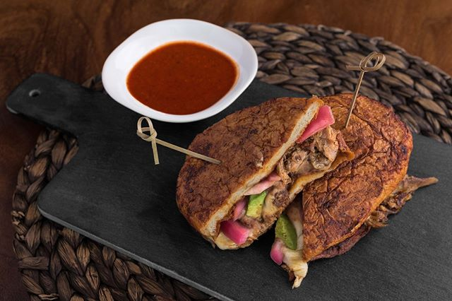 Spice up your Friday with our Torta Pambazo: citrus pork carnita, guajillo sauce, chipotle, avocado, pinto beans, chorizo sausage, pickled onions and tomato salsa on Mexican-style bread 💃🏽
