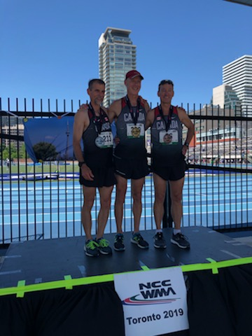 Mark Pinckard (Centre) receives his Gold Medal for the 1500m