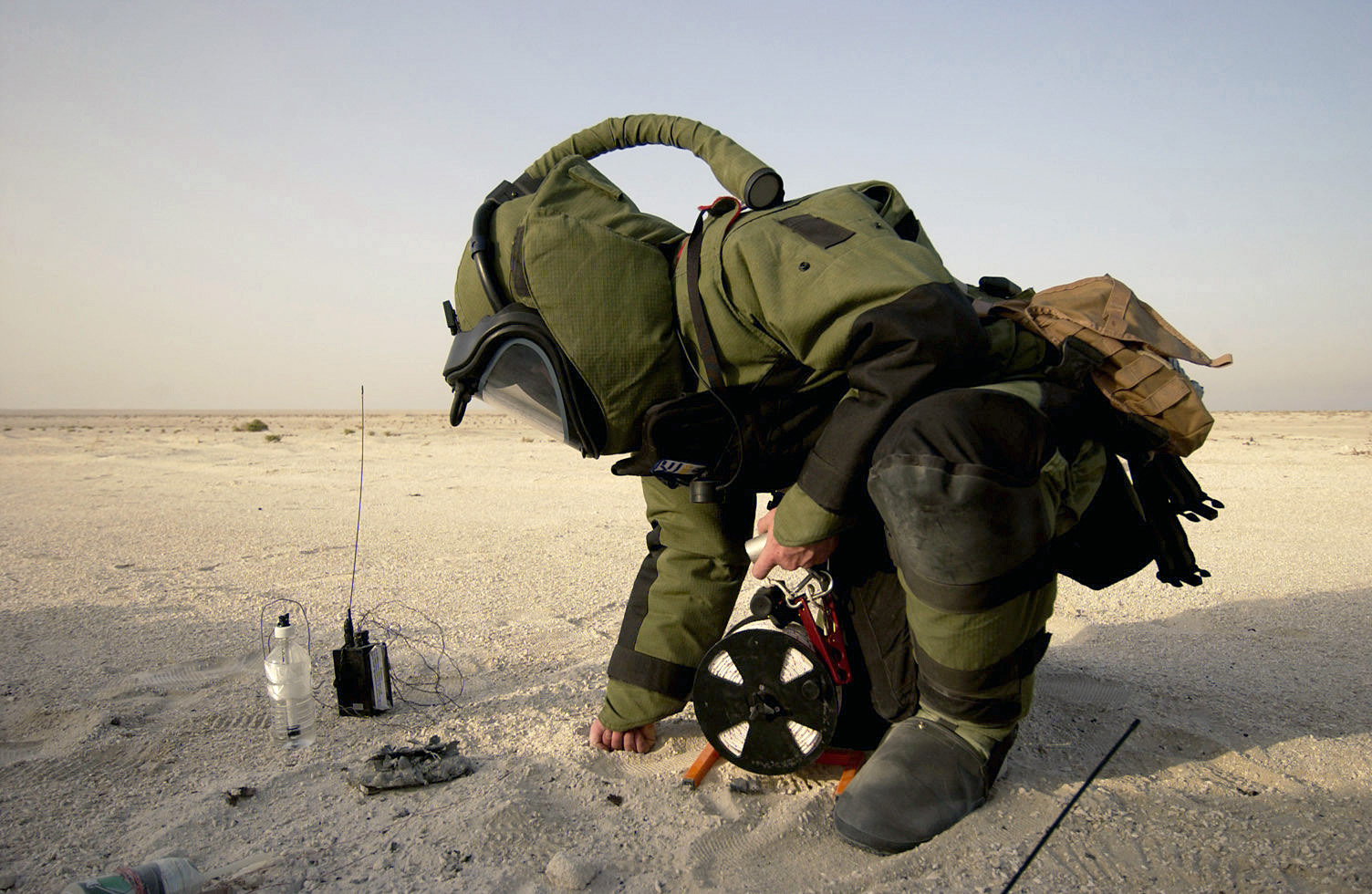 EOD technician investigating a wire in the desert