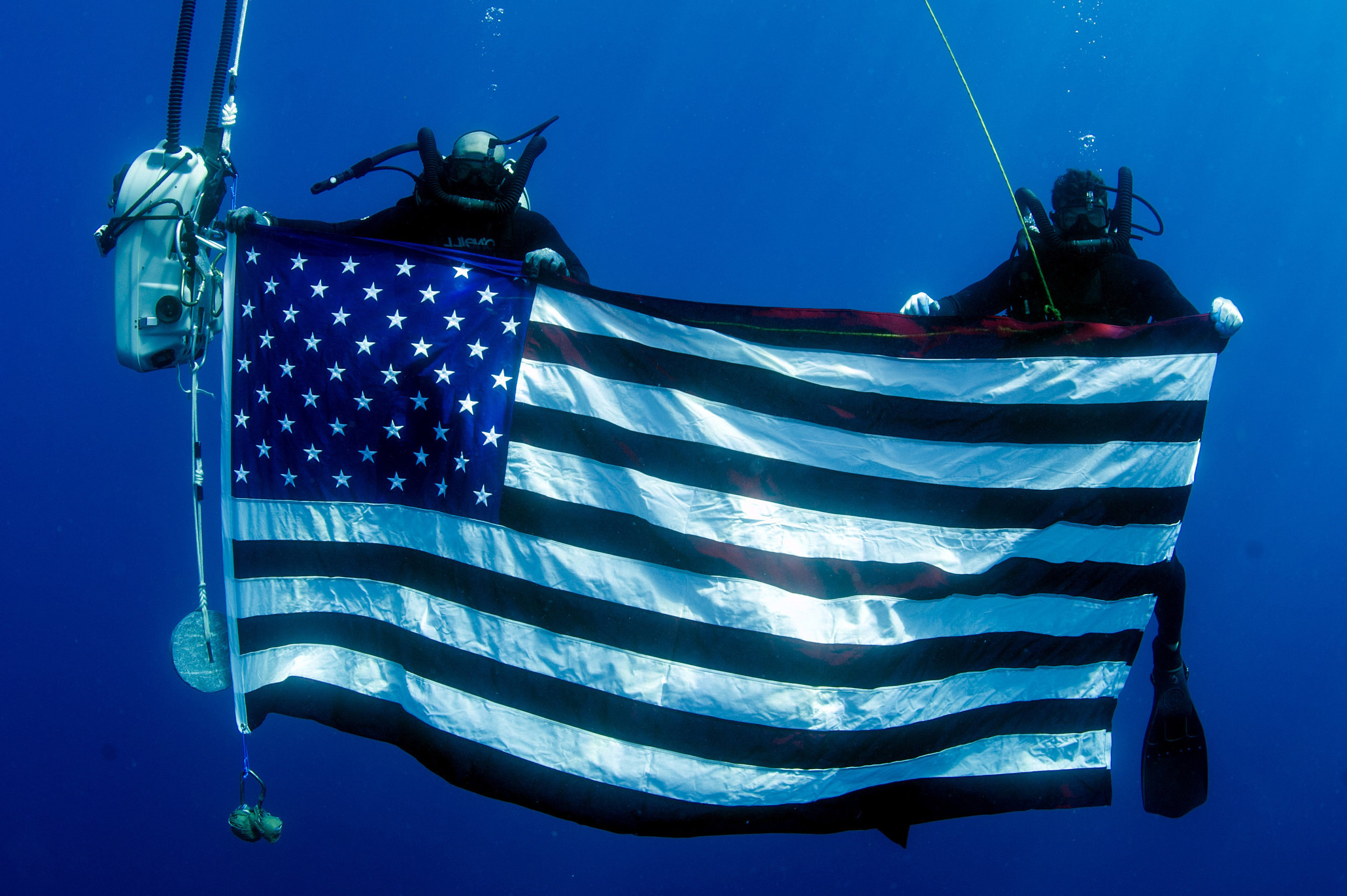 2 divers holding an American flag under water
