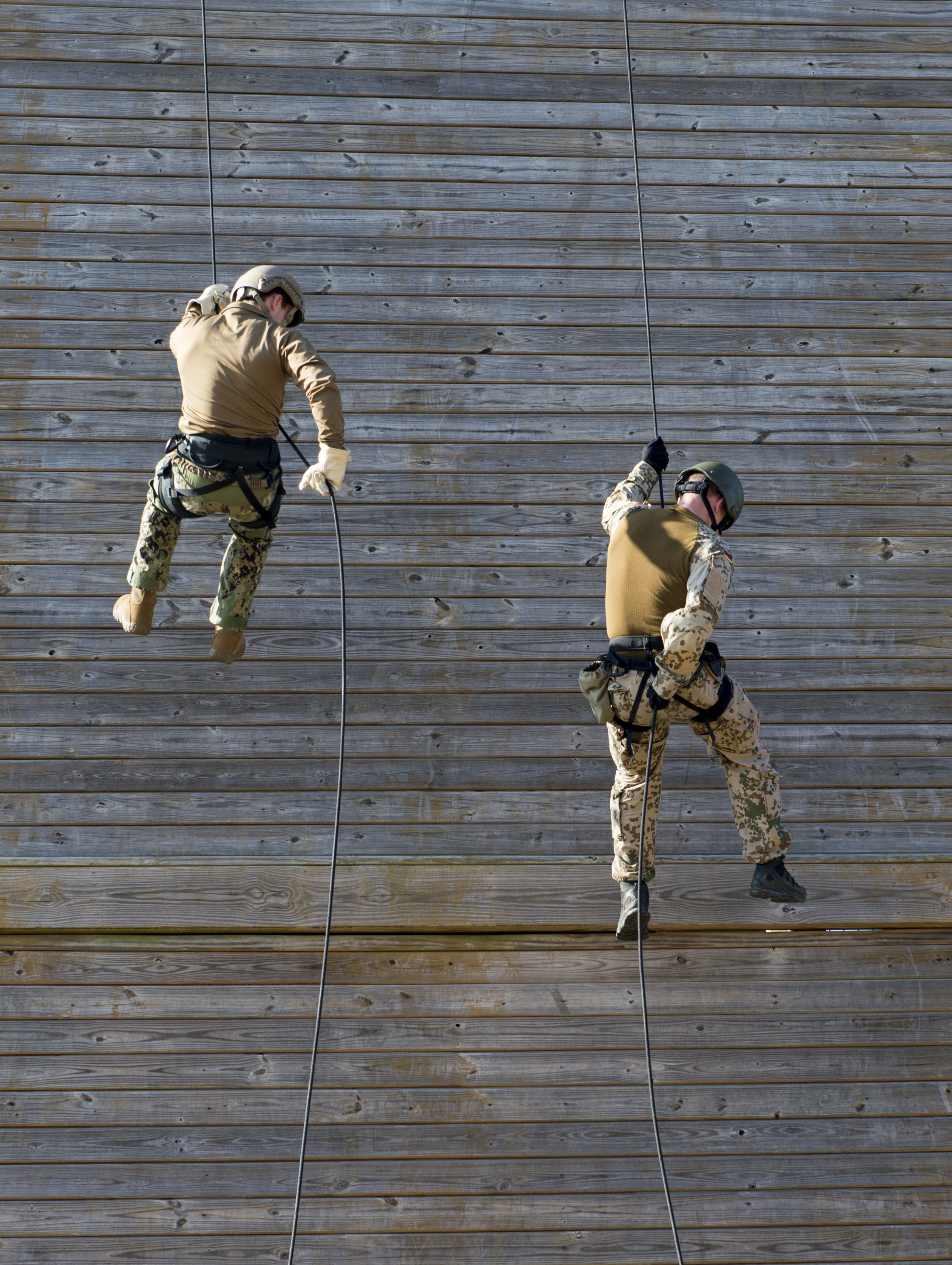 2 people rappelling down the side of an obstacle course