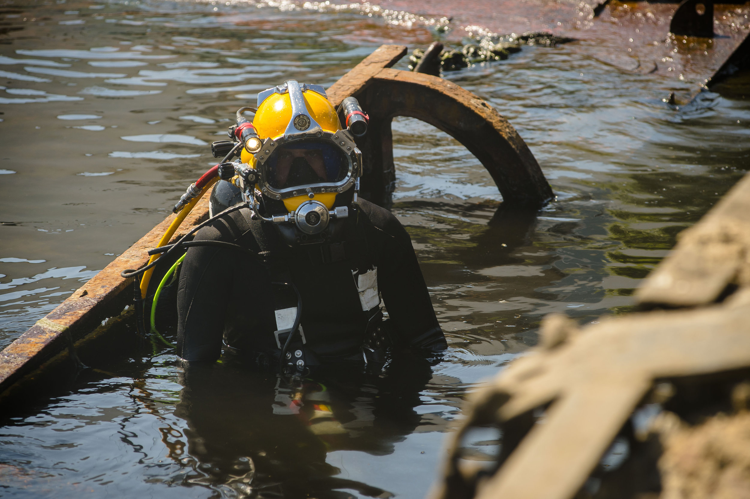 navy diver standing in water with full gear