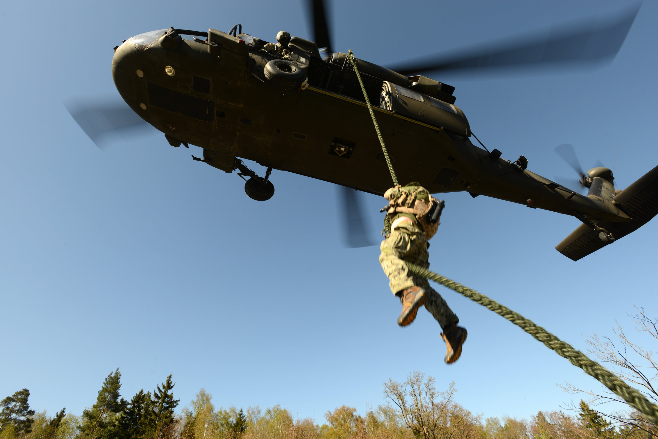 Navy SEAL rappelling down from helicopter