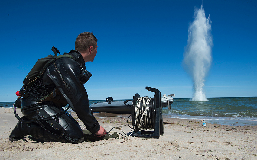 EOD Technician setting off an underwater explosive from the shore