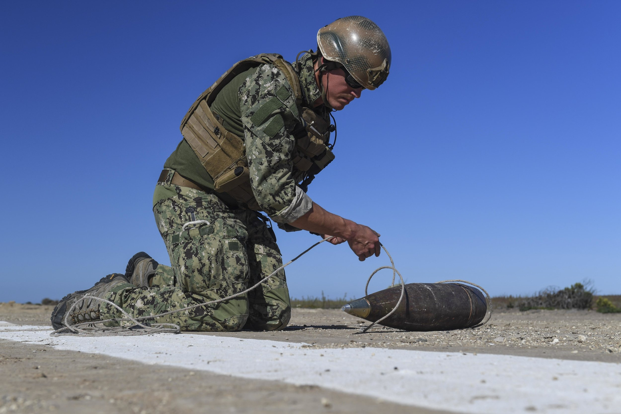 EOD technician investigating unexploded EOD