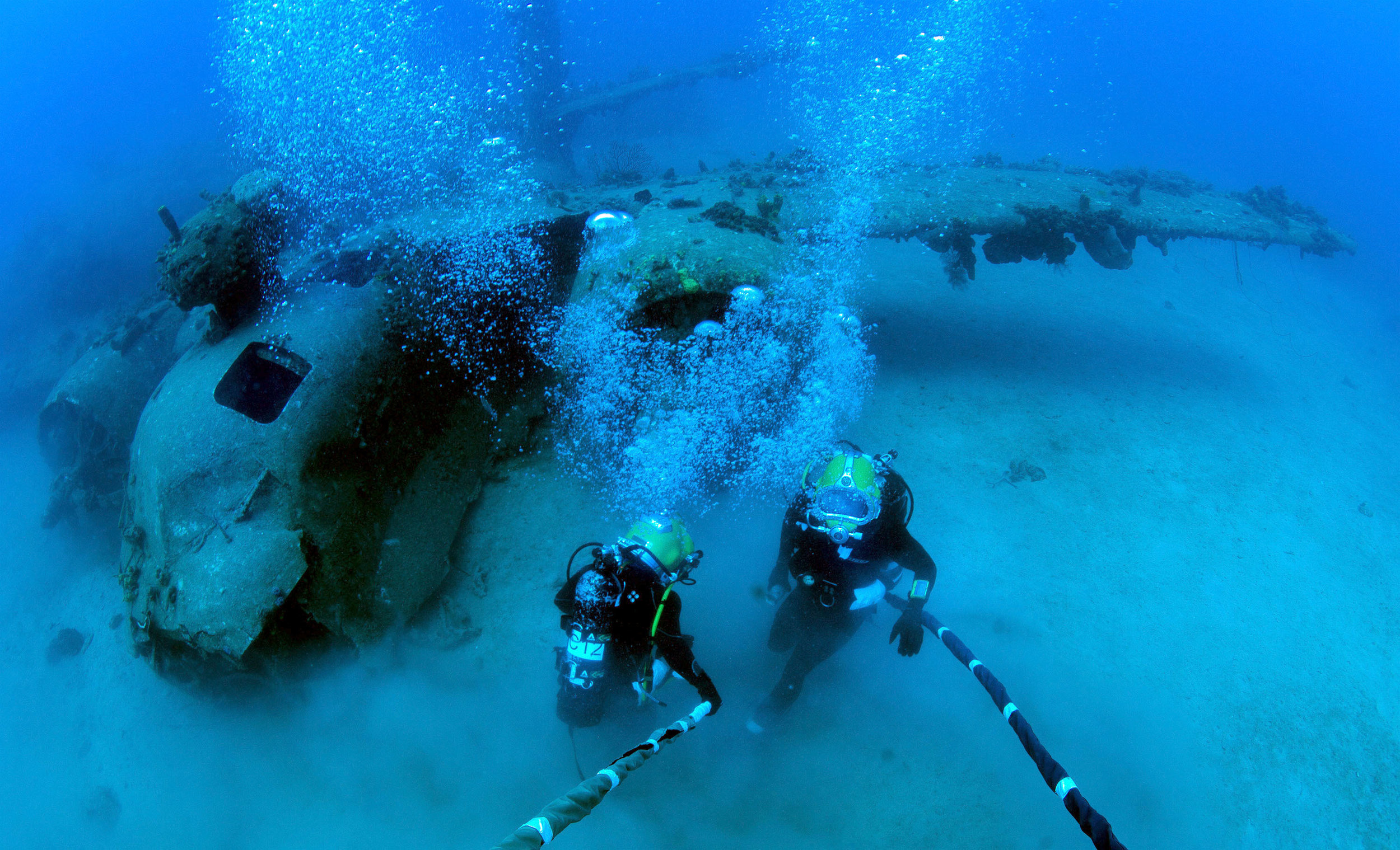 2 navy divers exploring a sunken aircraft