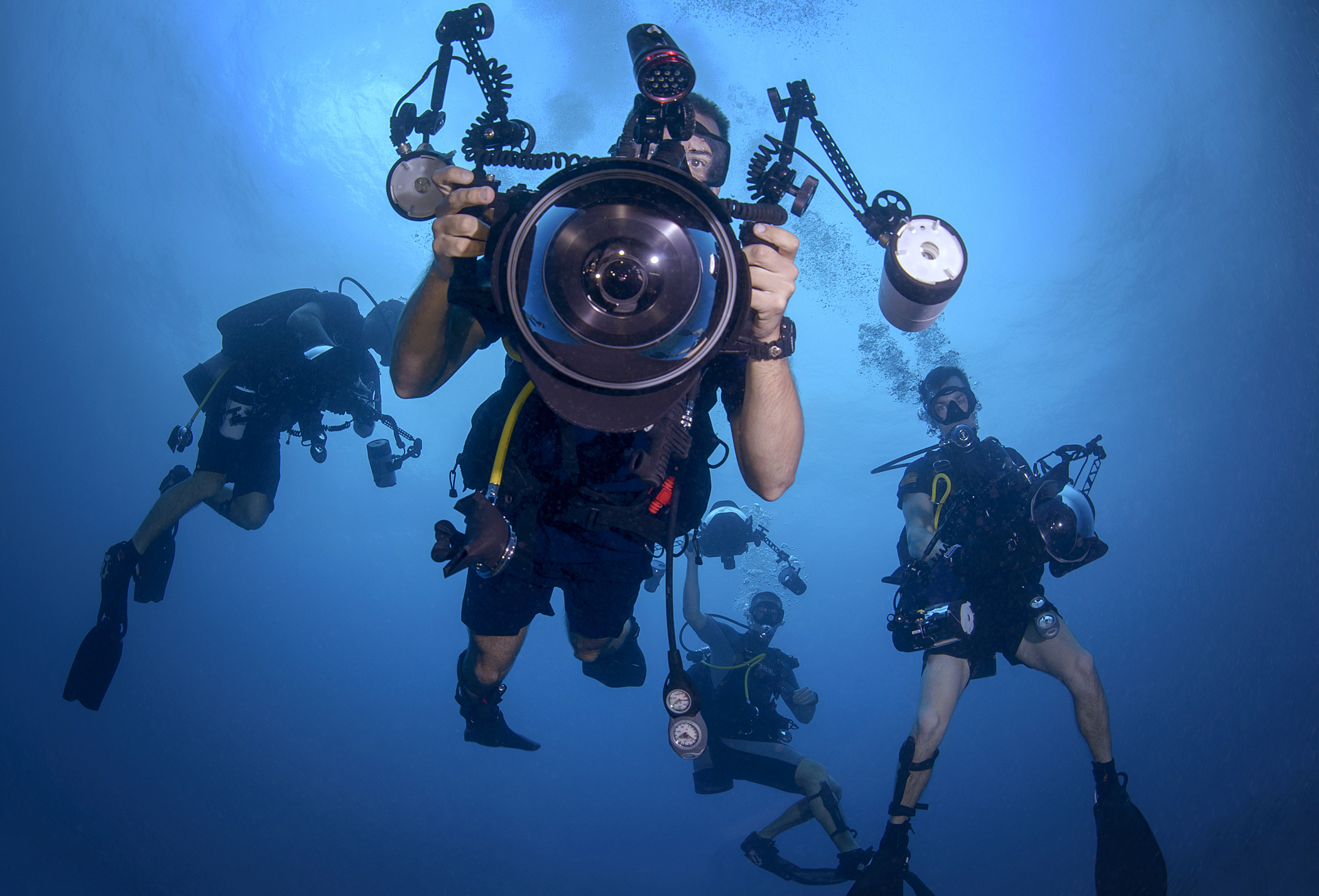 navy diver photographer taking picture with team underwater