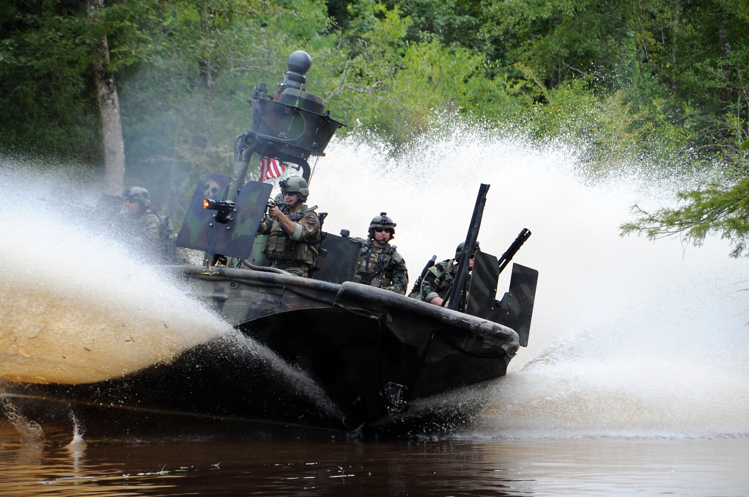 Special warfare combatant team in boat ready for action
