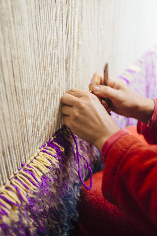 A weaver knotting a pile knot, or zerbiya. She threads the weft back and forth through the warp continuously until the rug is complete.The weft is separated with rows of knots tied around the warp.