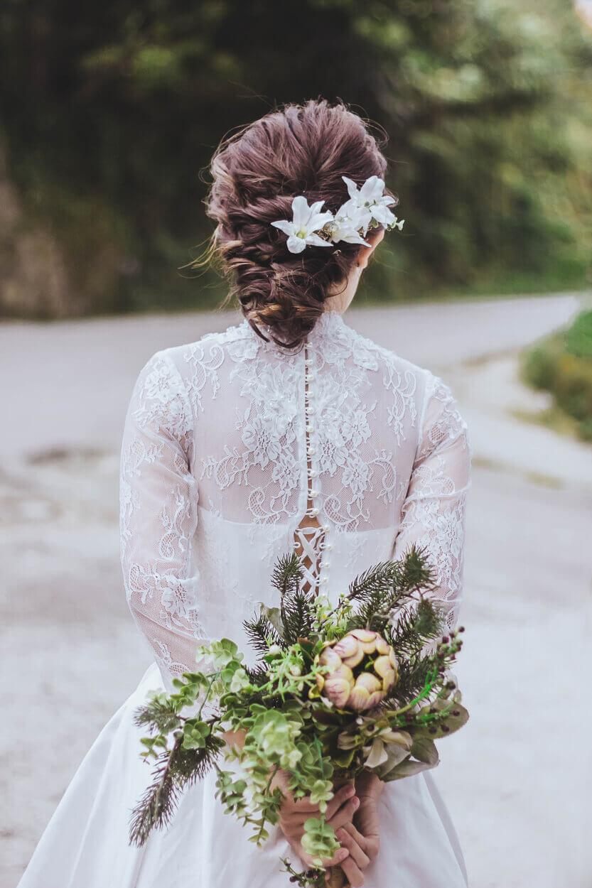 mariée de dos tenant un bouquet dans ses mains
