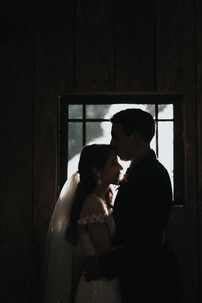 marié embrassant la mariée sur le front
