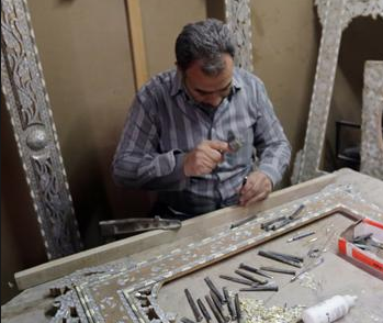 A Syrian artisan etches away at wooden panels inlaid with mother-of-pearl, at a workshop in Damascus on December 1, 2015 (AFP photo)