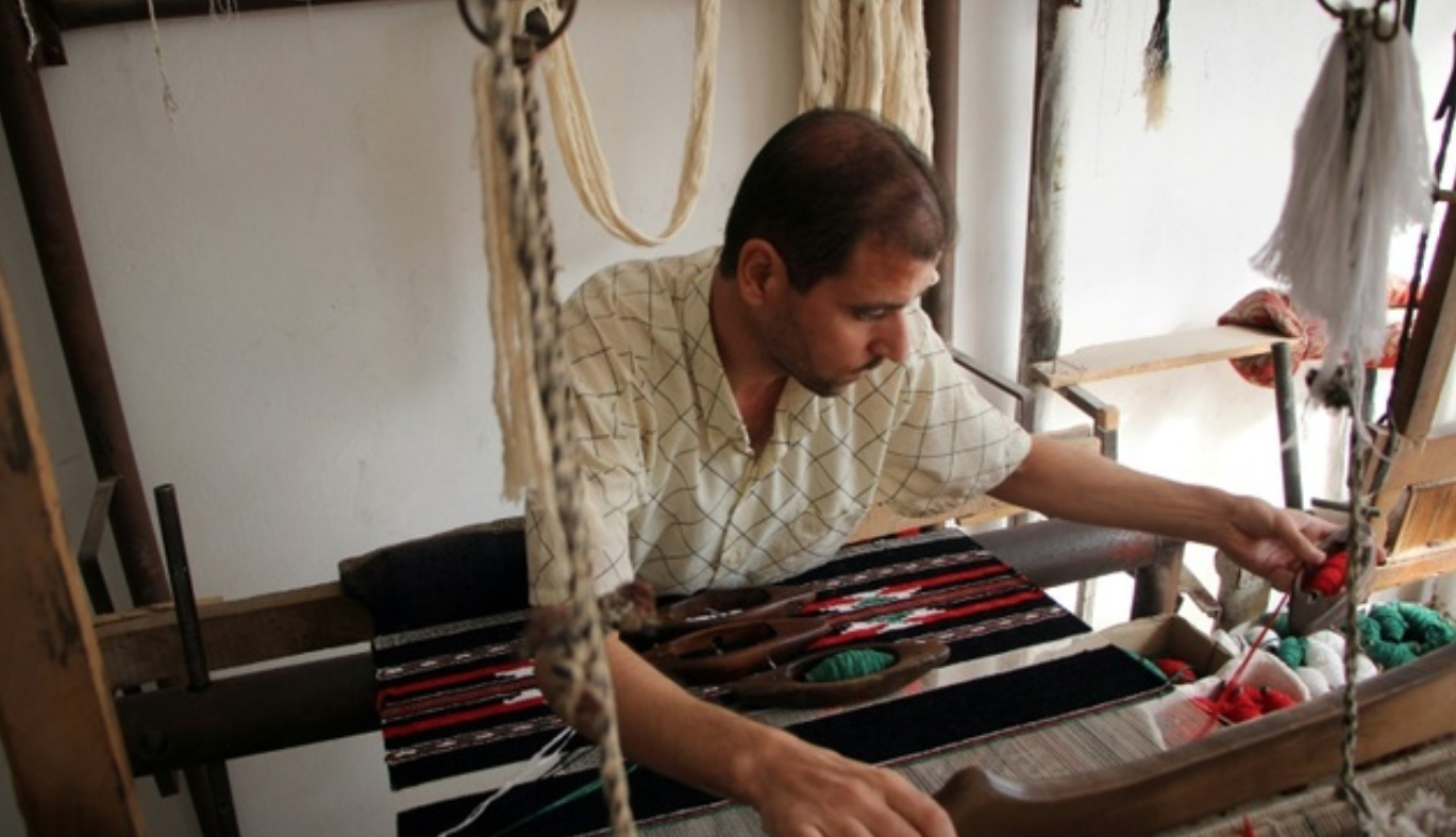 Syrian weaver Abu Ahmed works his loom on the last day before the workshop is forced to close due to a lack of thread imported from conflict-ridden Aleppo