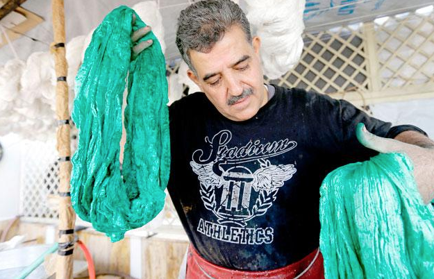 Mohammad Al Rihawi dips silk threads into green dye on January 23, at his atelier in the Syrian capital Damascus (AFP photo)