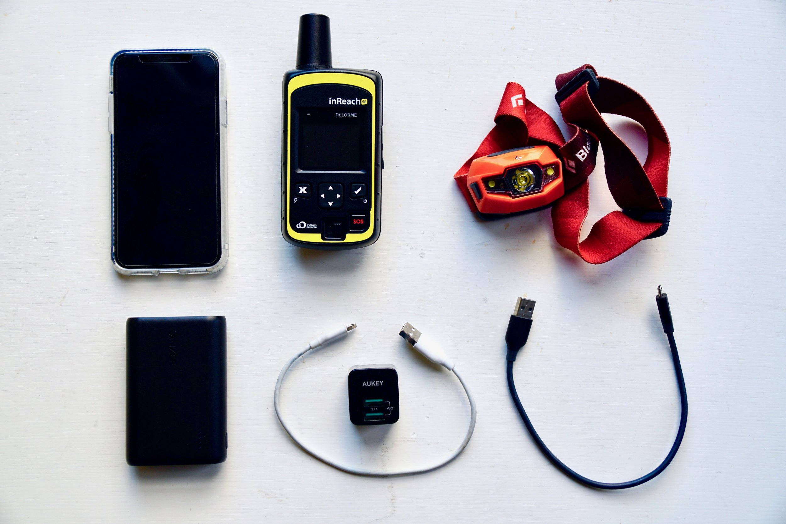 Electronics and communication : iPhone, InReach for emergencies, Black Diamond Revolt USB rechargable headlamp, Anker 10,000 mAh battery, charging cables and plug.