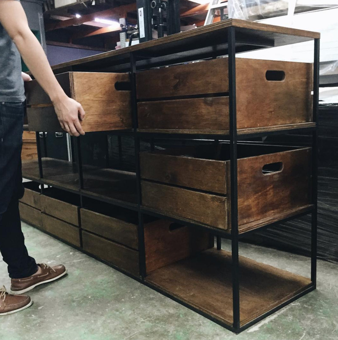 Plywood shelf with matte black steel frame and removable crates for On The Table
