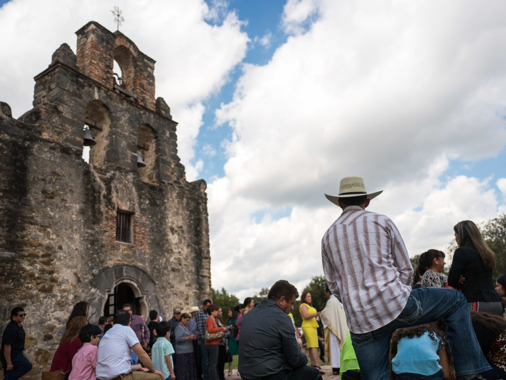 Community members congregate outside of the historic Mission San Francisco de la Espada in San Antonio, Texas, following a church service.  (Scott Ball, Rivard Report)