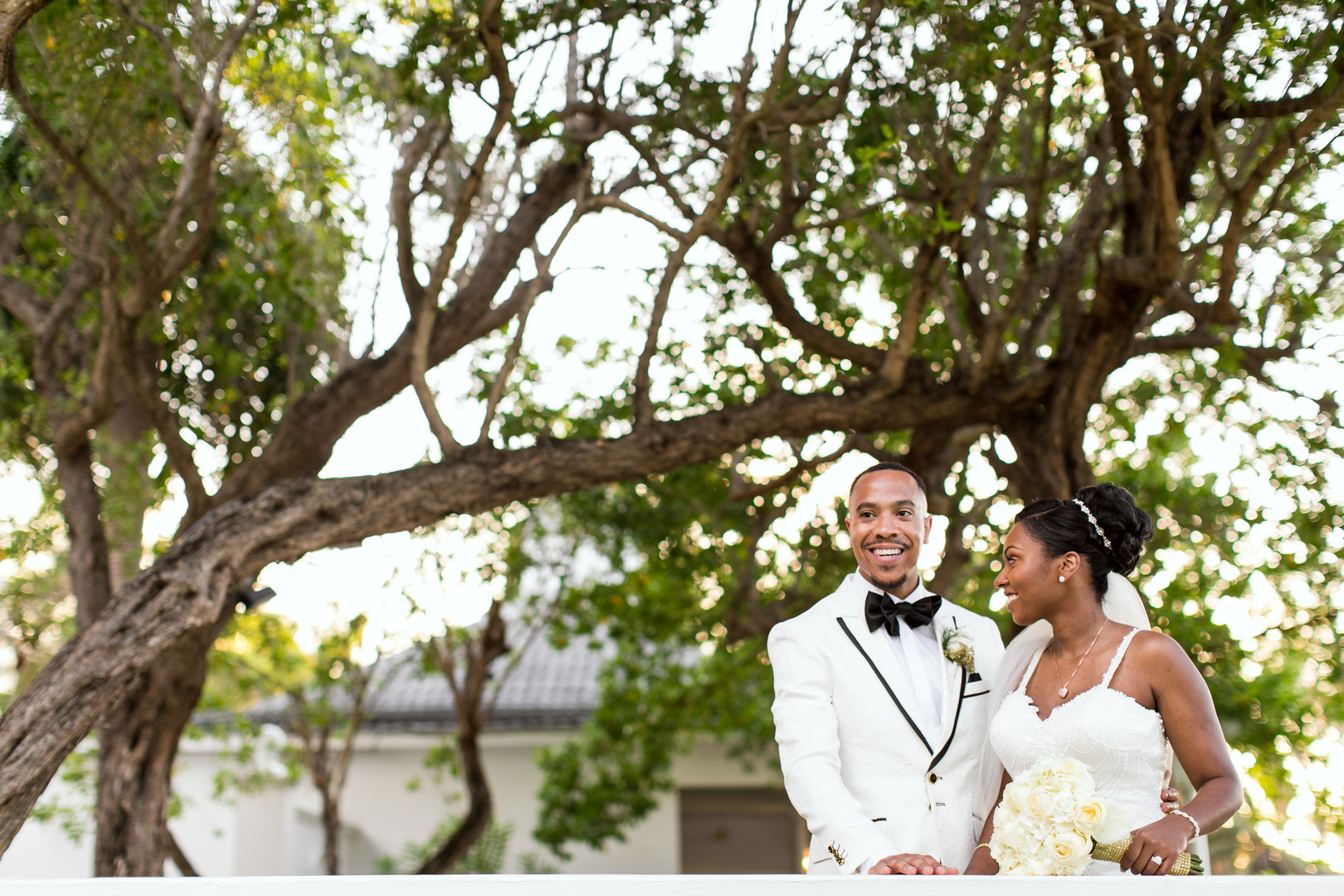 groom in white tux with black bow tie