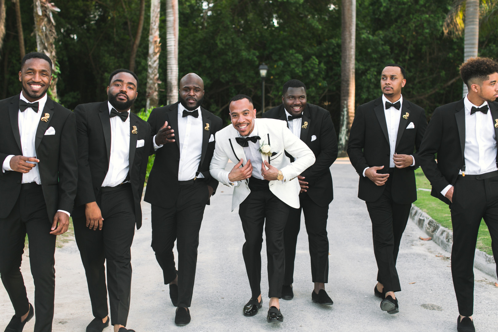 groom in white tux and groomsmen in black