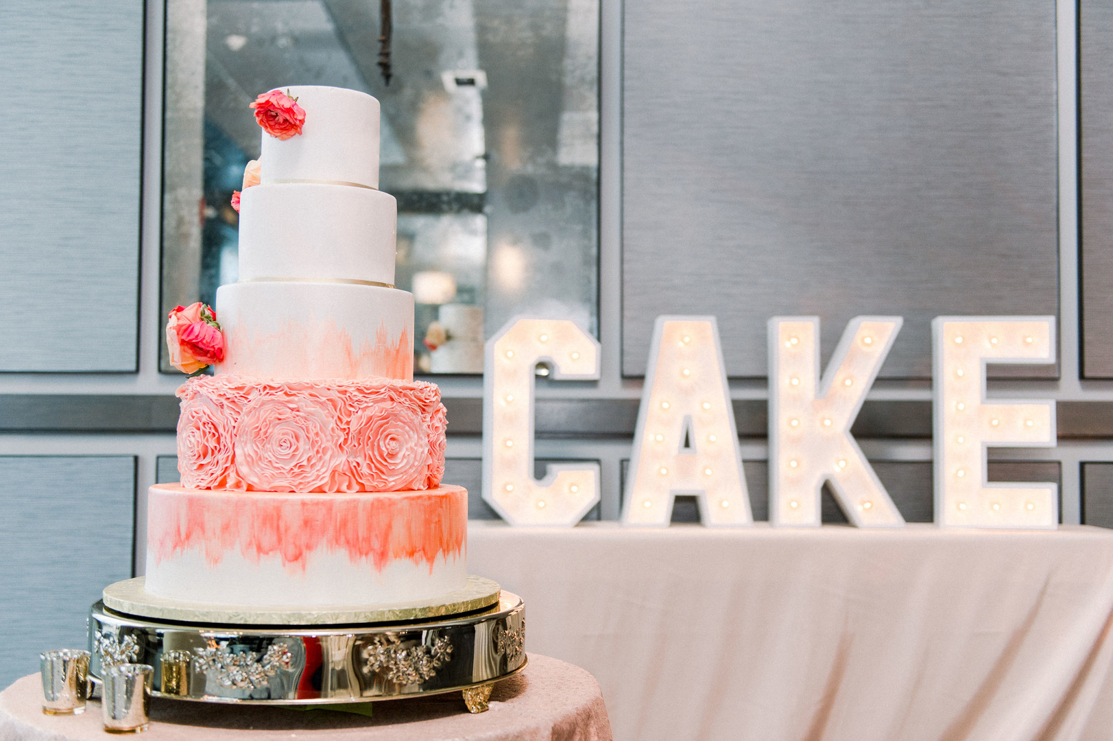 pink wedding cake on gold stand