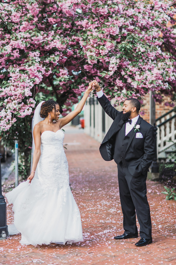 black bride and groom under tree in bloom