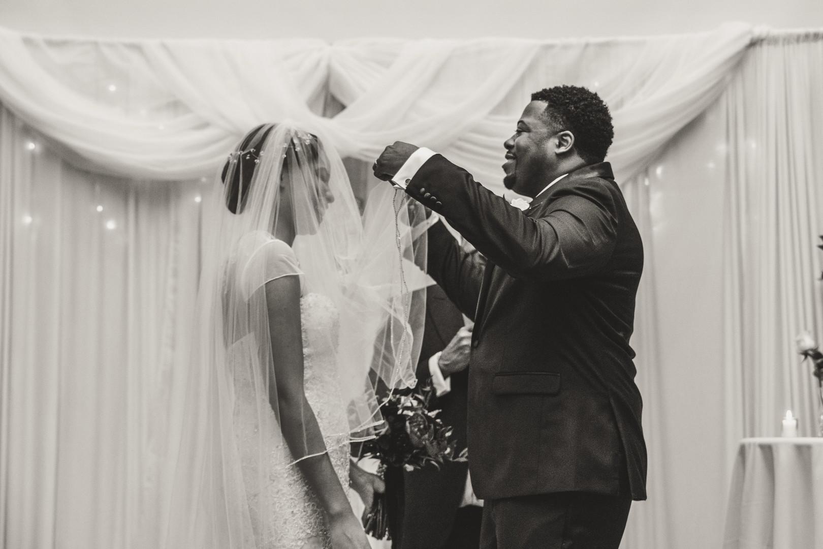 black groom lifting veil