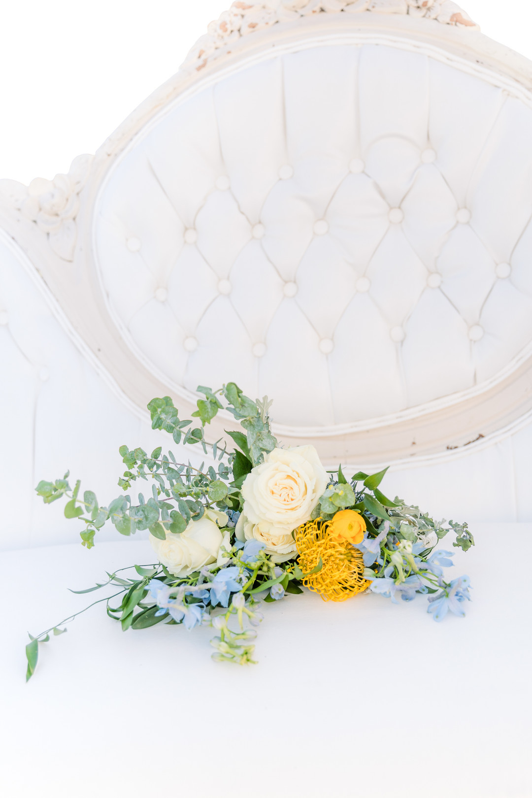 yellow and cream bouquet on white tufted couch