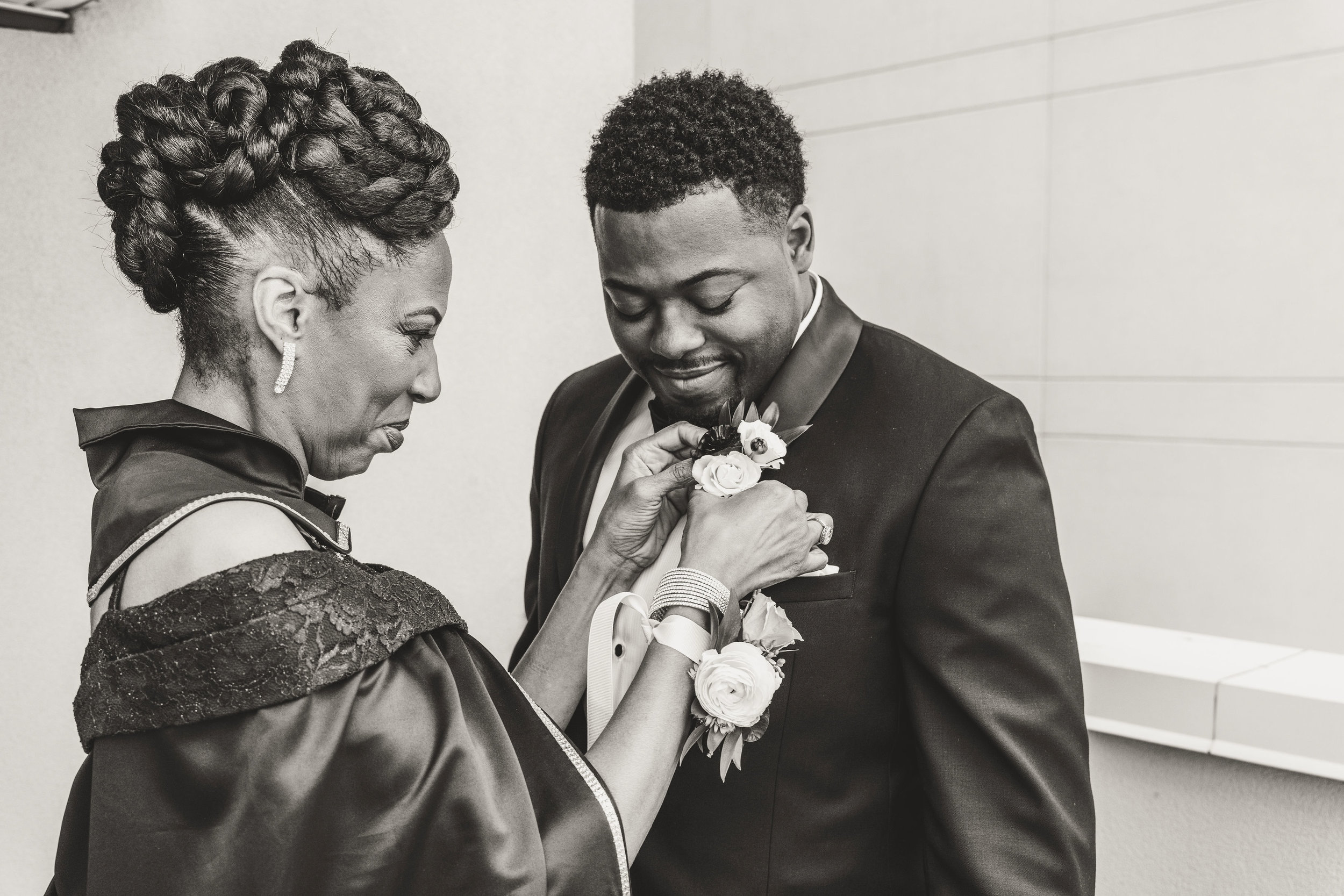 black mom putting on grooms boutonniere