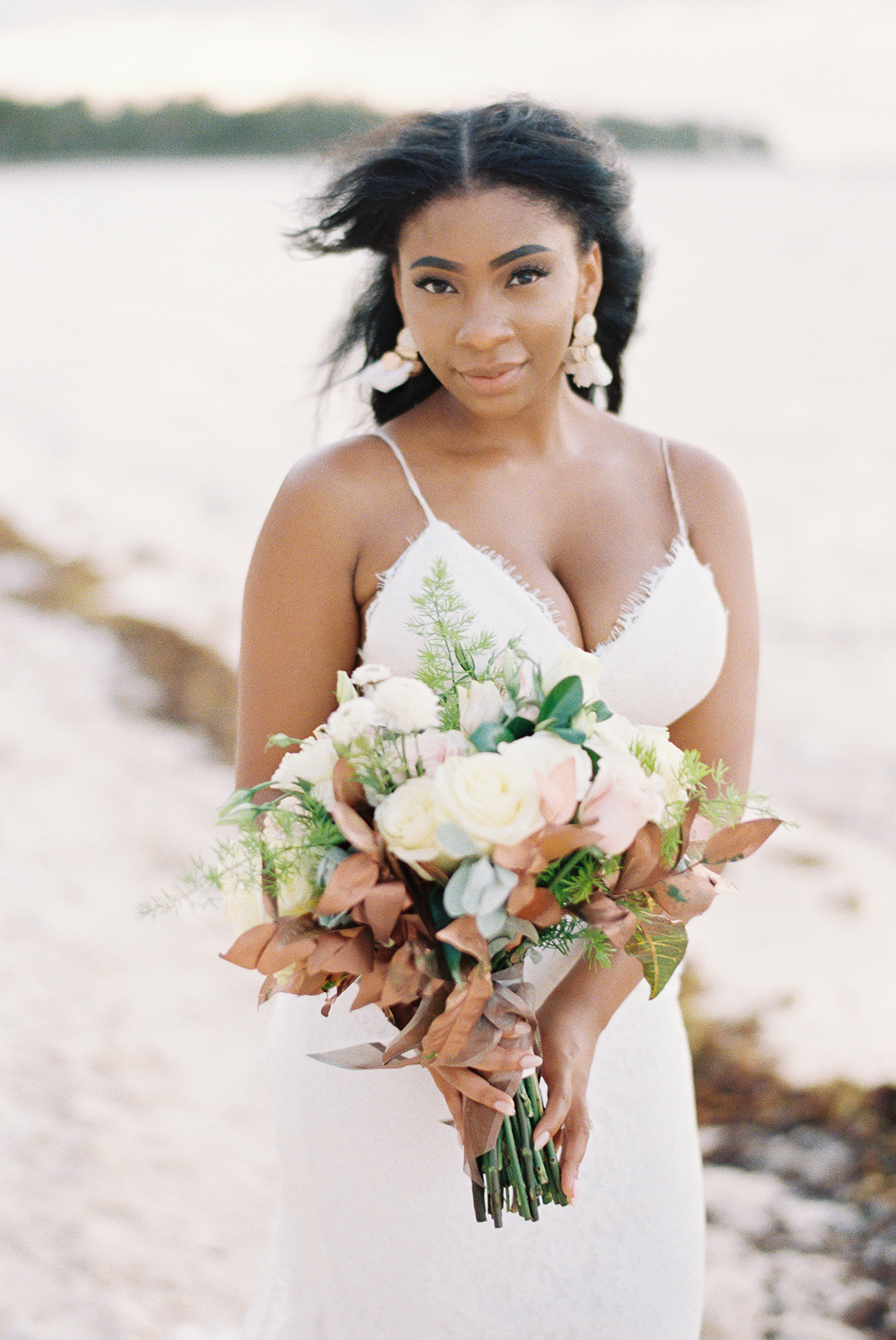 bride on beach holding bouquet