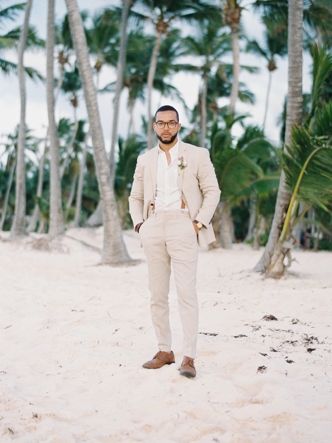 black groom on beach in tan suit