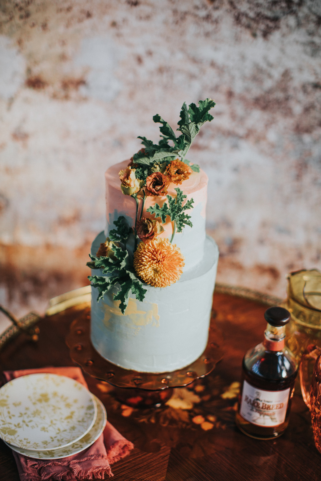Orange and pastel color wedding cake with rustic flowers