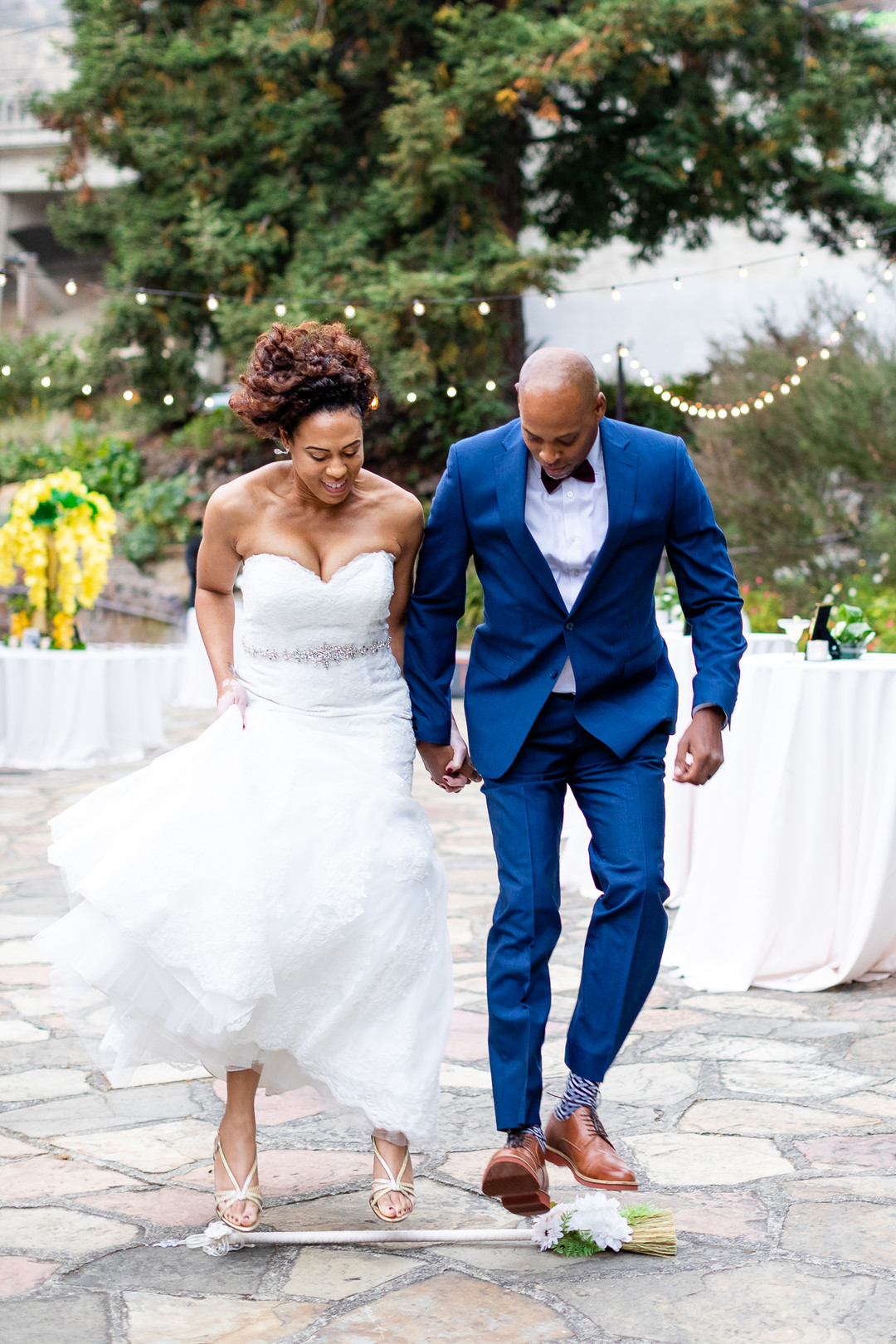 African American bride and groom jump the broom