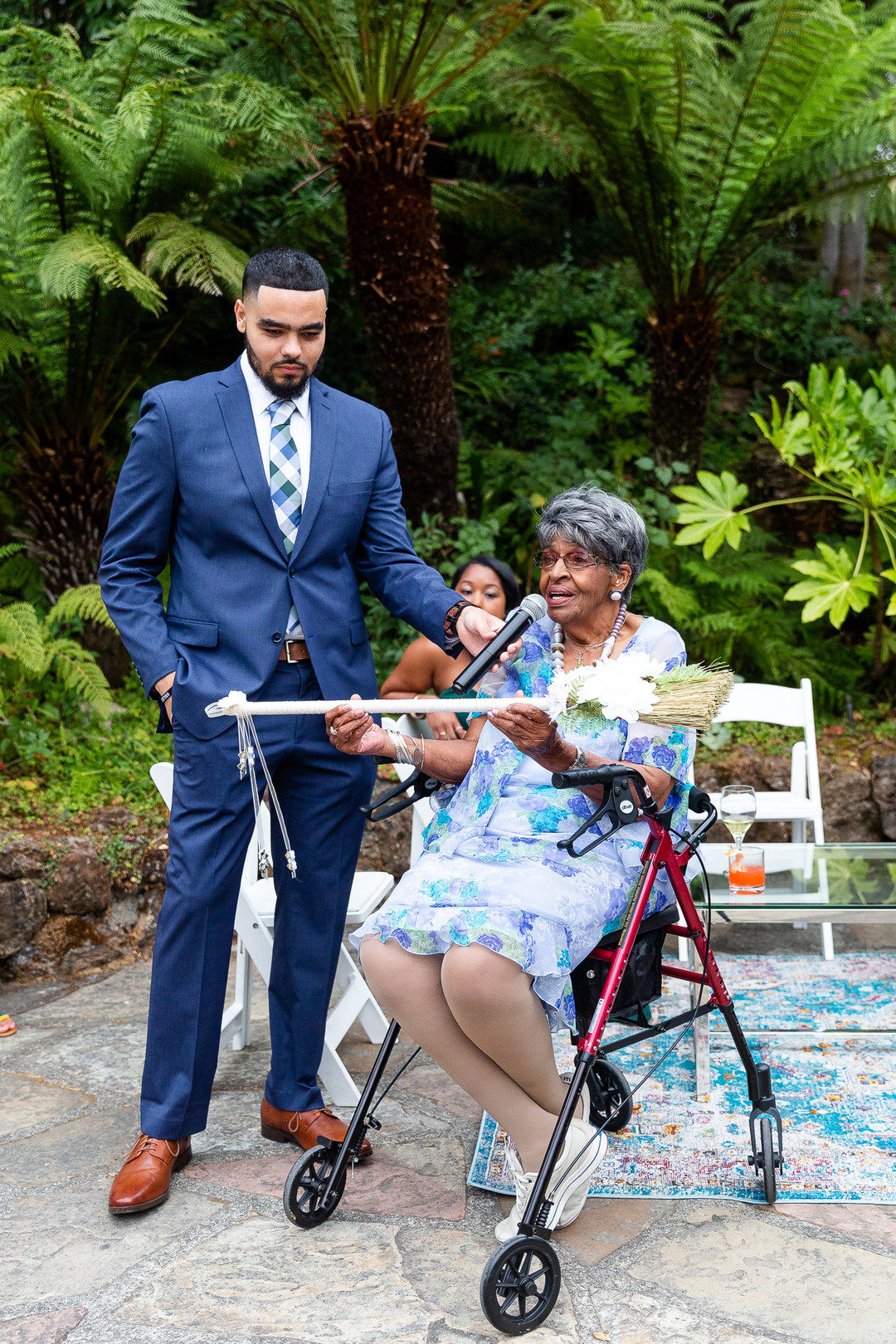 elderly relative blessing the couple while holding broom