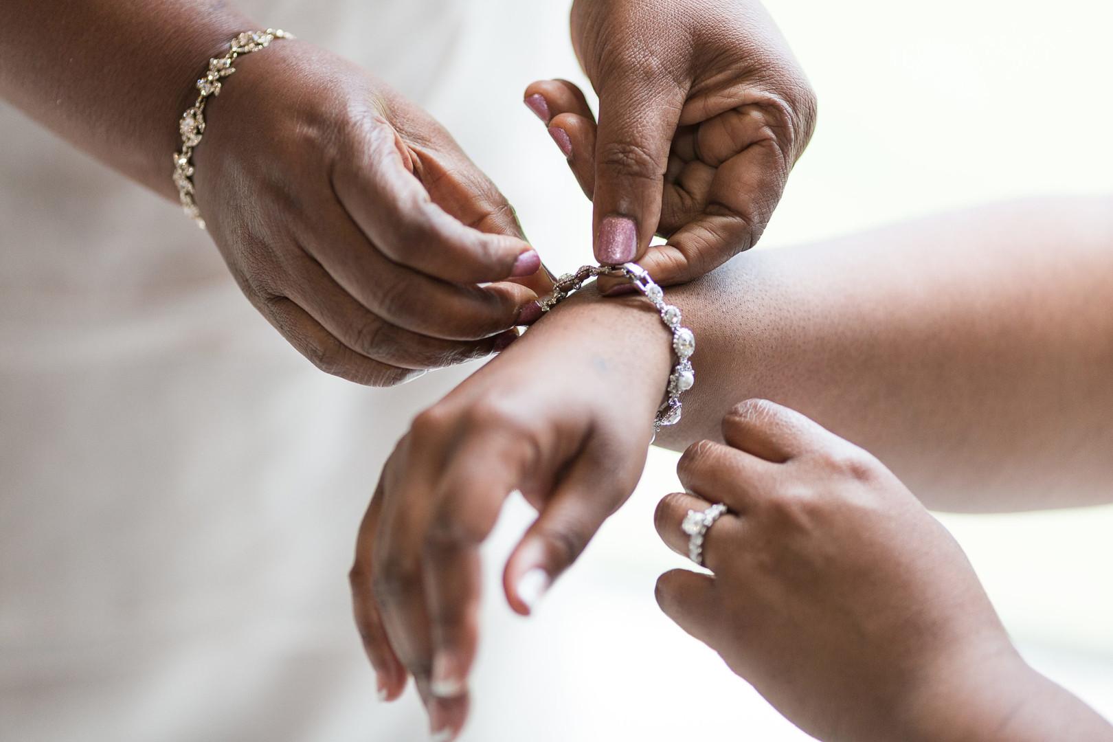 mom putting on bride's wedding jewelry